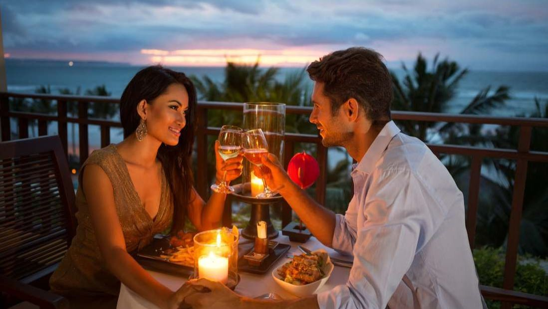 Couple at romantic dinner by beach at night