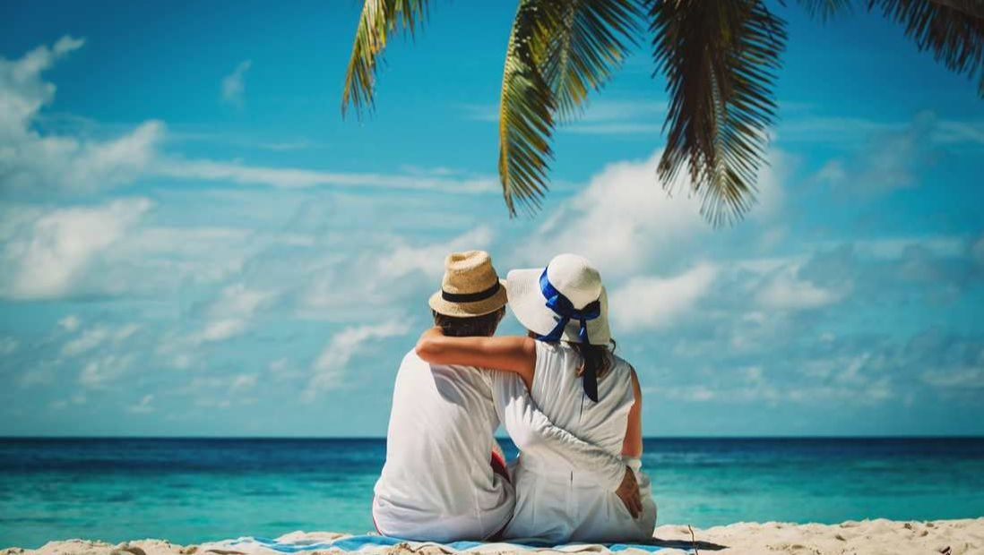 Couple sitting by beach in the sand under a palm tree